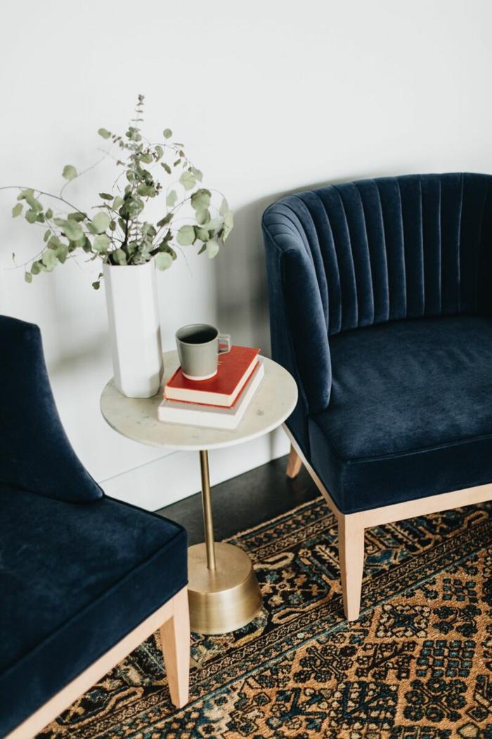 deux fauteuils en tissu velours en bleu roi avec des pieds bas en bois clair, tapis oriental, table sur pied haut ronde et blanche, murs blancs, renover meuble bois
