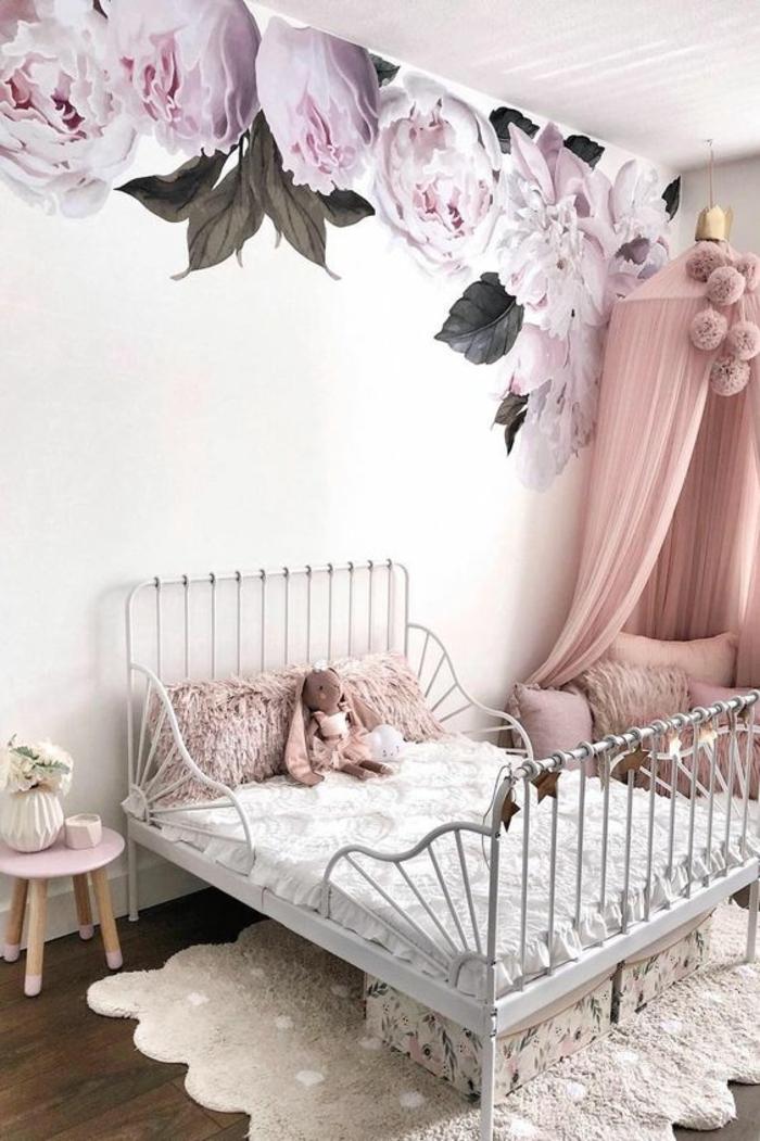 chambre rose poudree avec papier peint aux gros motifs fleuris, pivoines blanches et rose poudré, lit en métal aux barreaux nuances argentées, petite table ronde avec quatre pieds en bois clair