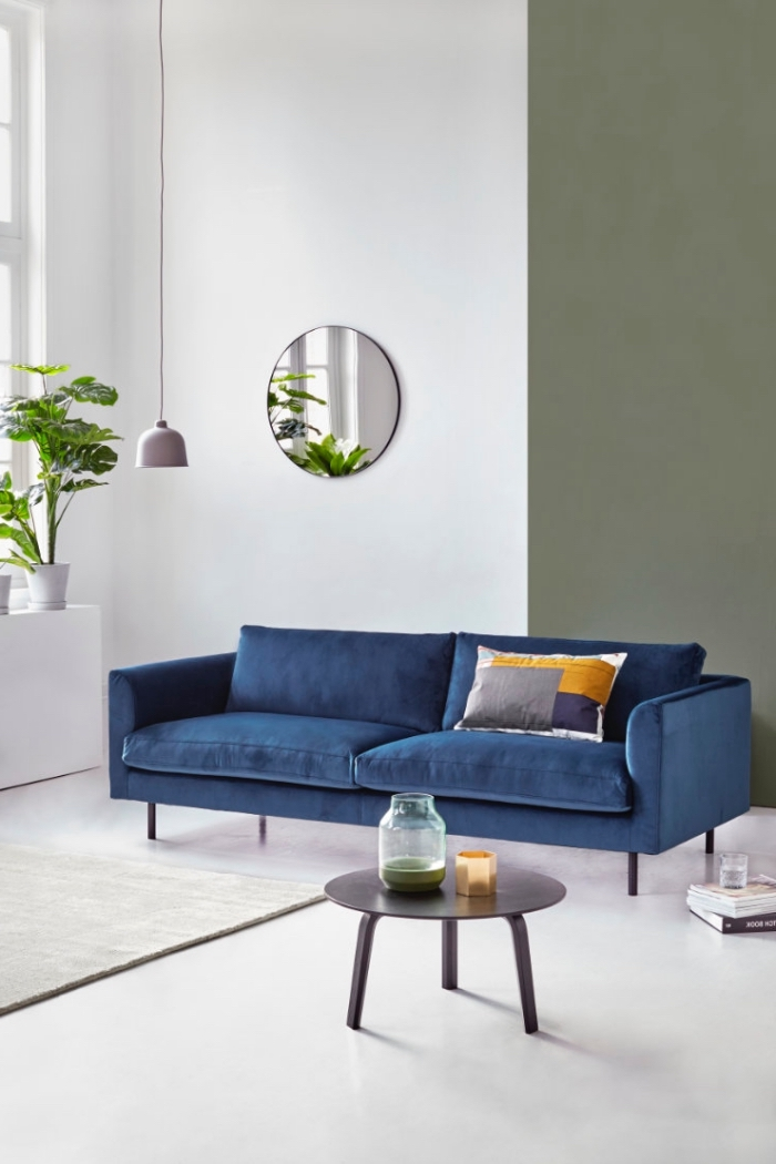 ambiance naturelle et apaisante dans un salon blanc, vert et bleu, canapé bleu marine design met en valeur par un coussin imprimé gris, jaune moutarde et bleui indigo