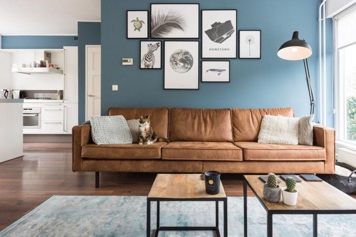 comment réussir la deco bleu canard dans un salon moderne, les touches de noir, le cuir marron et les éléments boisés mettent en valeur la luminosité du bleu canard