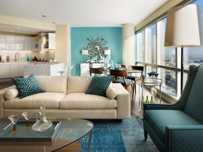 un mur bleu canard au fond du salon avec salle à manger qui s'harmonise avec les nuances du bleu turquoise et les murs couleurs lin