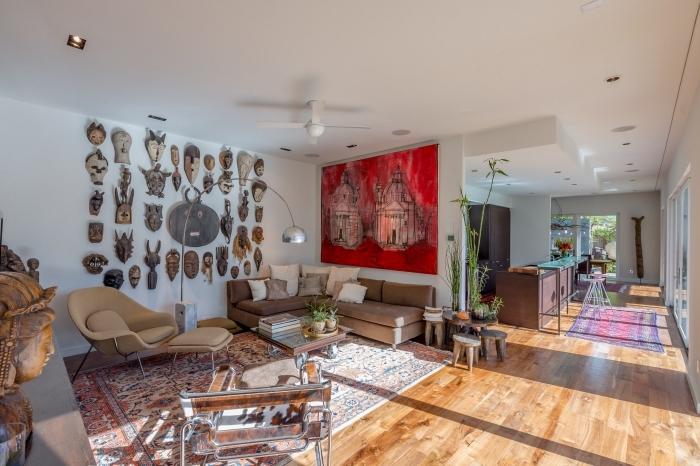 design intérieur de style africain dans un salon ouvert aux murs blancs avec plancher de bois et mur de masques africaines