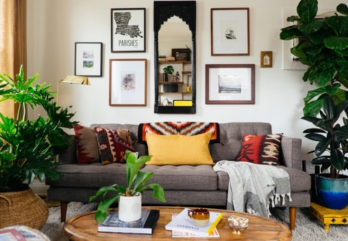 ambiance ethnique dans un salon traditionnel aux murs blancs avec mur de cadres photos et miroirs, modèle de table basse bois