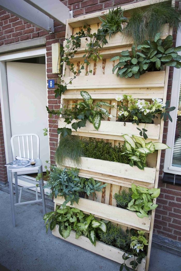 une jardinière réalisée avec des palettes récupérées, comment réaliser un mur végétalisé avec des matériaux récup