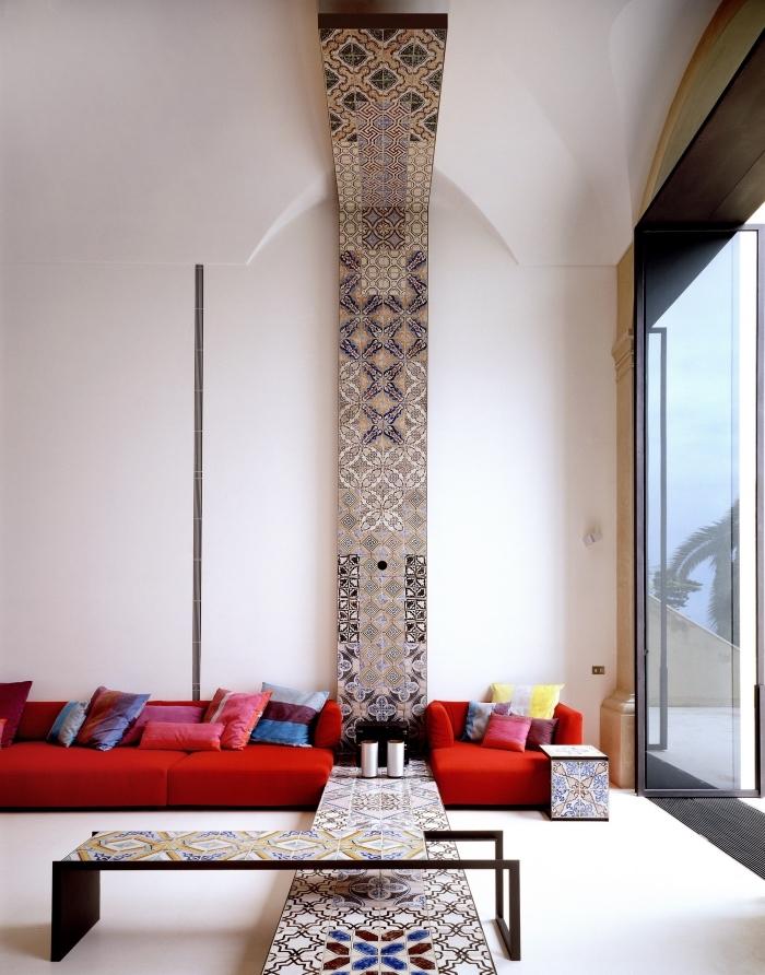 large salon aux murs blancs avec grande fenêtre et déco ethnique chic, modèle de canapé bas et long rouge
