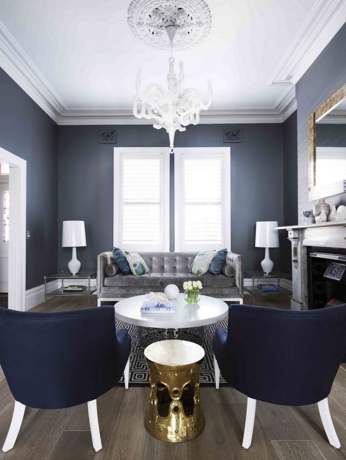 la couleurs bleu nuit des murs et des fauteuils s'associe aux éléments déco en blanc et gris pour donner à ce salon vintage un aspect élégant et chic