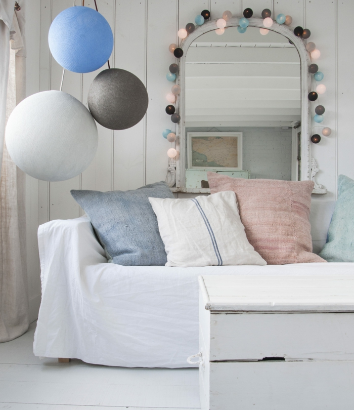 salle de séjour, salon, guirlande boule coton multicolore, boules en couleurs pastels, suspendues au-dessus du cadre blanc d'un miroir en forme semi-ovale