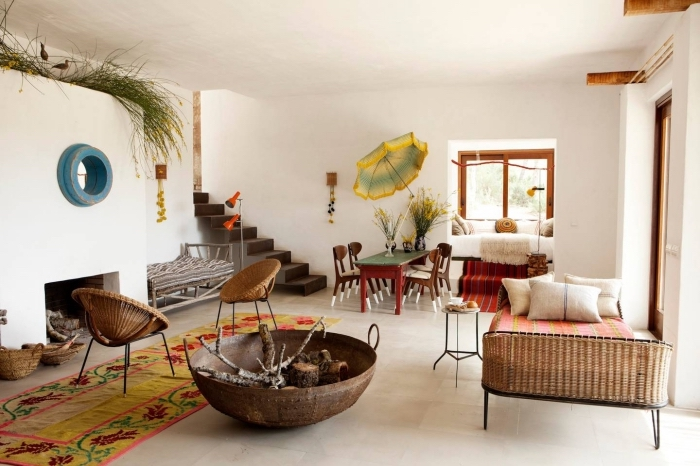 exemple de tapis ethnique coloré en jaune moutarde avec fleurs rouges, déco de salon blanc avec meubles de rotin