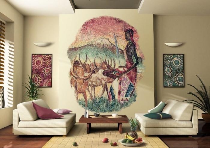 esprit africain dans un salon beige aménagé avec canapés bas et table basse de bois foncé, déco murale avec peinture paysage africain
