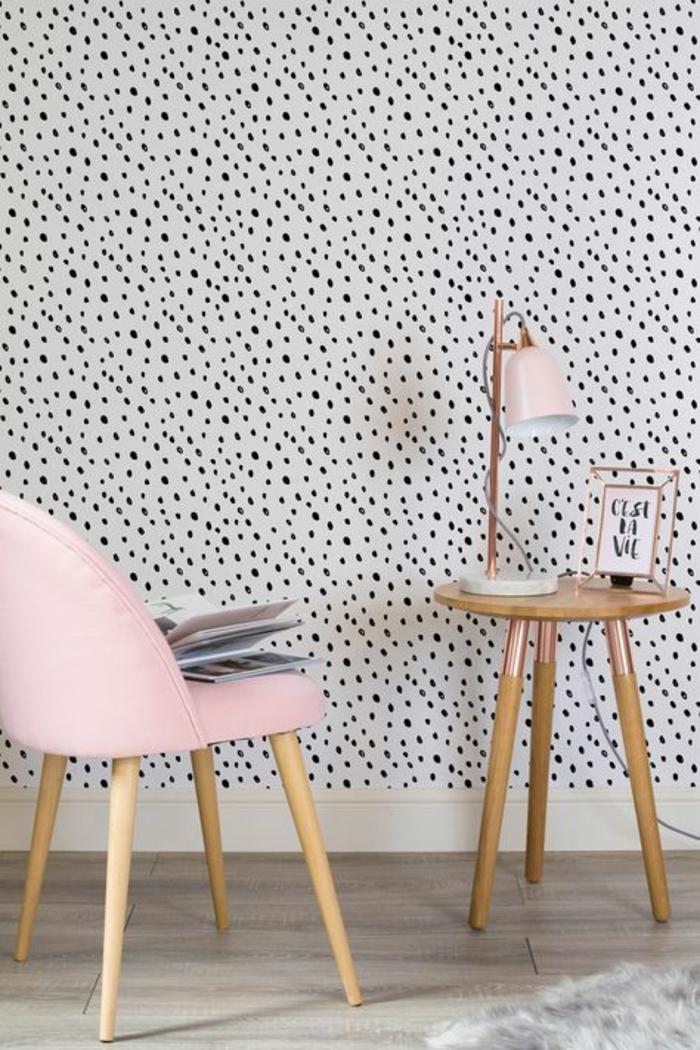 couleur rose pale, meubles en rose poudree, murs revêtus de papiers peints blancs aux pois noirs, table ronde avec trois pieds en bois clair