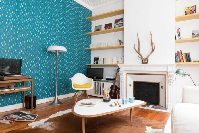 un mur bleu canard dans un salon blanc et bois d'ambiance scandinave, papier peint imprimé vintage en bleu vert saturé qui s'harmonise avec l'intérieur blanc et le bois blond
