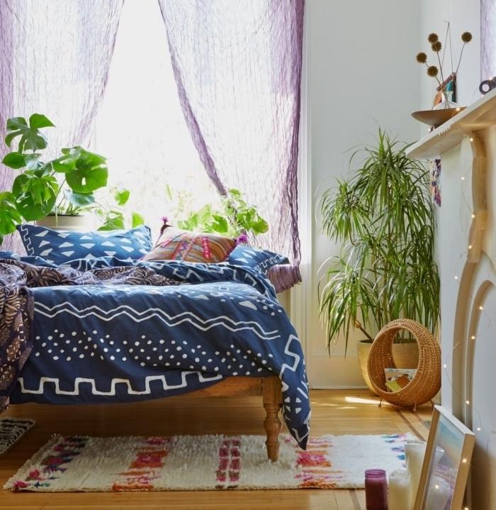 design intérieur de style hippie chic avec lit en bois couvert de coussins décoratifs et housse en bleu canard aux motifs blancs