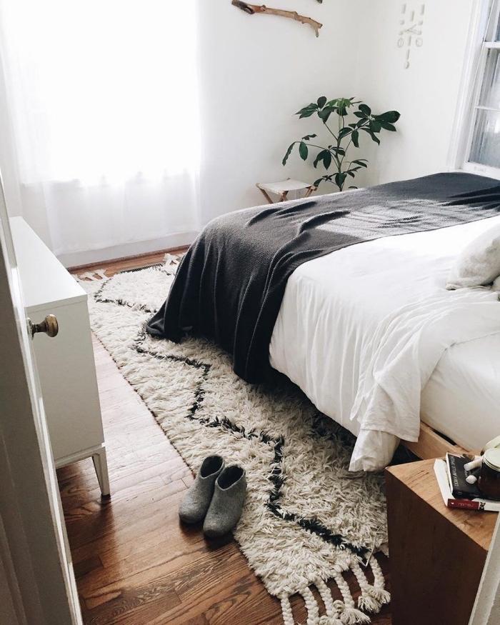 modèle de tapis bohème de couleur beige et noir avec frange sur plancher de bois foncé dans une pièce blanche