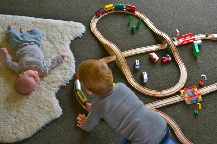 chambre montessori, peau d'animal blanche au pelage court, enfant qui joue avec ses trains et bébé couche qui l'observe, jeux d'éveil, apprendre le mouvement