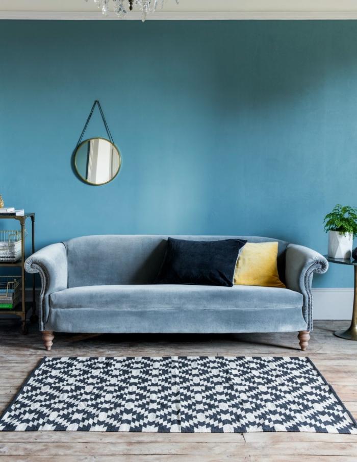 salon bleu paon qui décline la couleur sur les murs et sur le mobilier design, le petit miroir mural met en valeur la richesse et la luminosité du mur