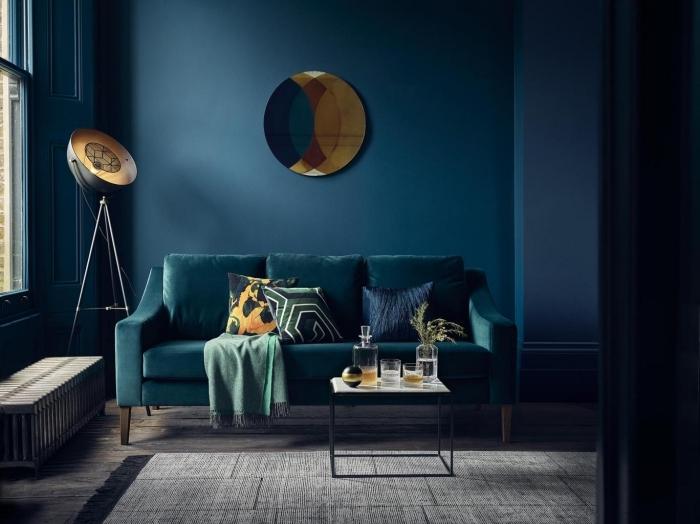 salon élégant et sophistiqué où la couleur bleu canard sur les murs et sur le canapé est mise en valeur par les accents déco lumineux
