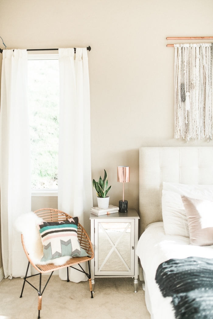 design intérieur moderne dans une chambre à coucher beige aménagée de style bohèle avec grand lit à tête boutonnée blanche et diy macramé