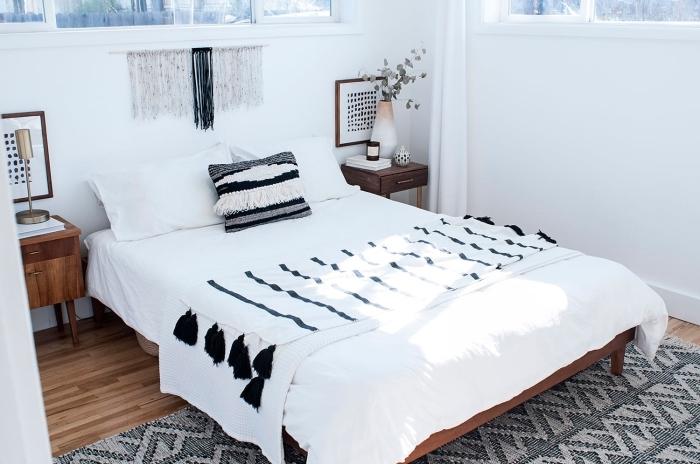 chambre blanche au parquet de bois avec large tapis aux motifs géométriques et table de chevet de bois foncé