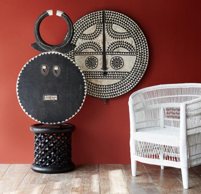 objets de décoration intérieure en style africain, idée comment aménager une pièce aux murs rouges avec éléments africains