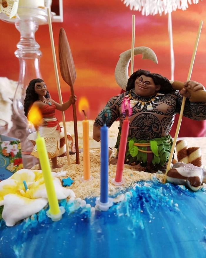 idée de décoration de gâteau sur le thème de Disney avec figurines des personnages Vaiana et Maui sur une couche de sable en biscuits émiettés
