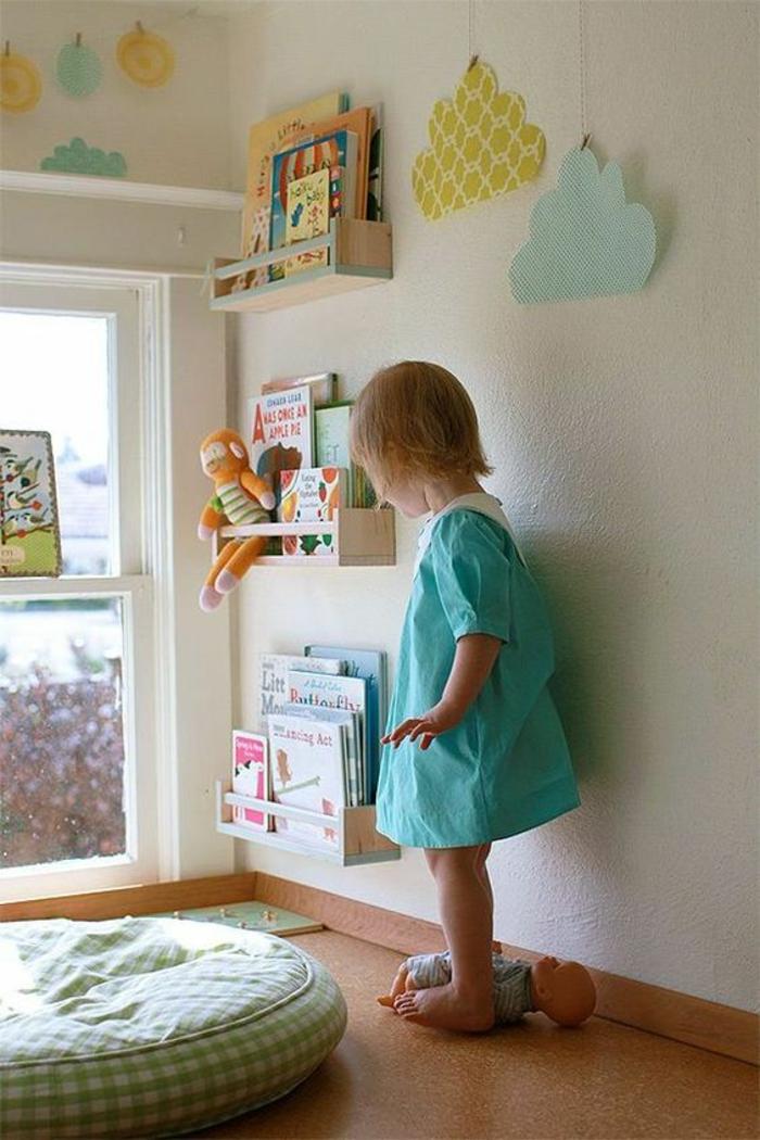 chambre montessori, meuble montessori, pouf rond marocain en tissu a carreaux blancs et verts réséda, fillette en robe vert menthe, étagères rangement livres a hauteur de l'enfant, parquet marron foncé, fenêtre au cadre blanc