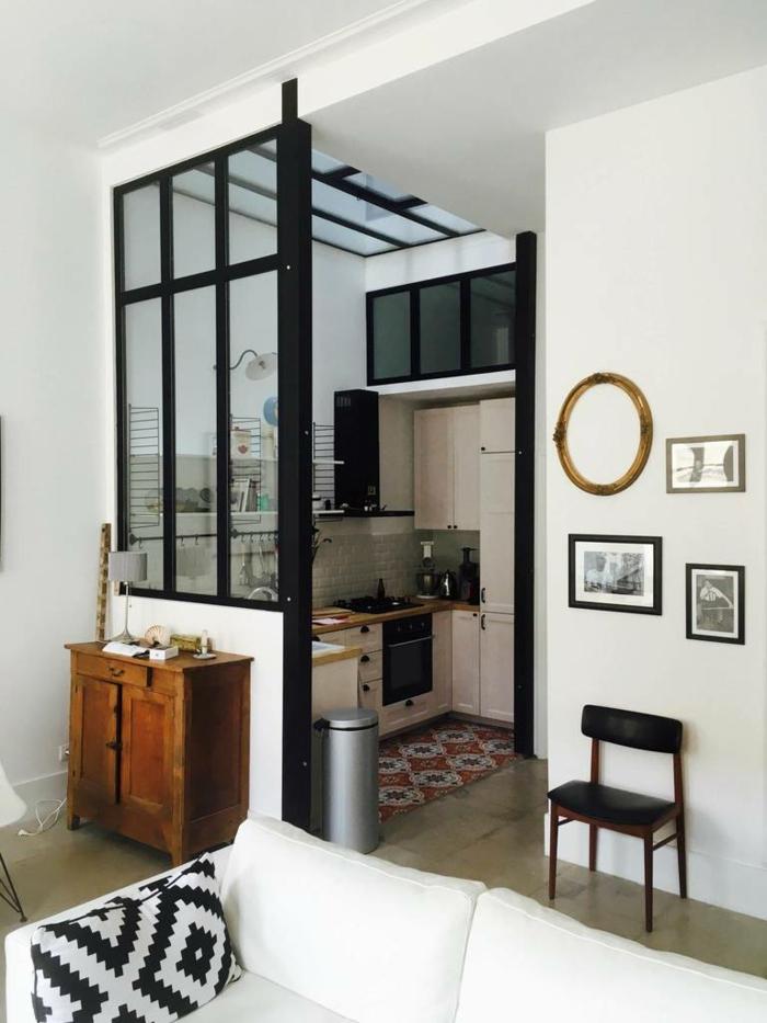 petite cuisine en l avec cloison vitrée noire style atelier d'artiste, buffet en bois rustique, grand sofa blanc, coussin géométrique