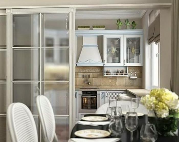 cuisine avec verriere interieure coulissante, chaises blanches et table noire ovale