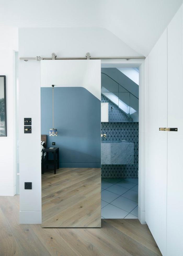 une porte de salle de bains coulissante belle et pratique, recouverte de miroir pour donner une sensation de profondeur dans la chambre à coucher adjacente, recouvrir porte interieure de miroir
