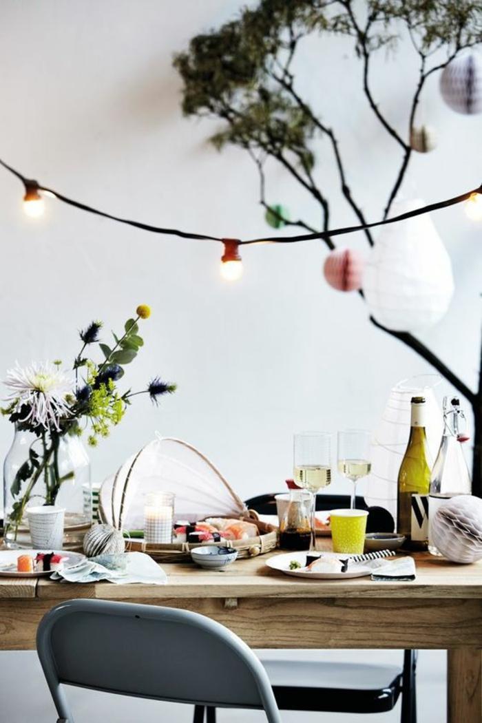 salle a manger, murs blancs, grande table rectangulaire en bois marron clair, chaise métallique pliable en gris perle, guirlande lumineuse pour chambre, guirlande lumineuse boule coton
