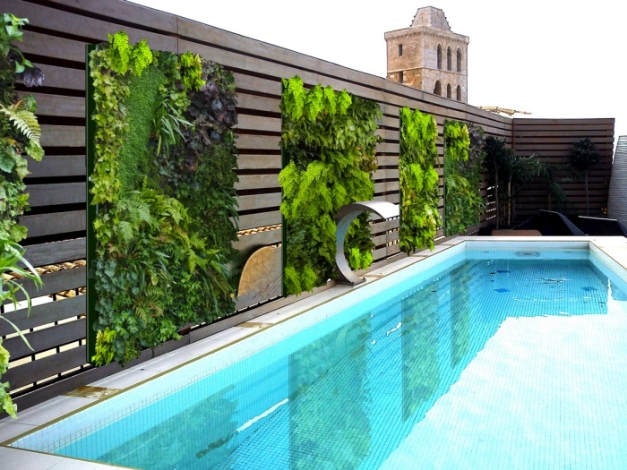une piscine de luxe avec des murs végétaux installés sur la palissade en bois façon qui agissent comme un brise vue vegetal tout en créant une ambiance propice à la détente