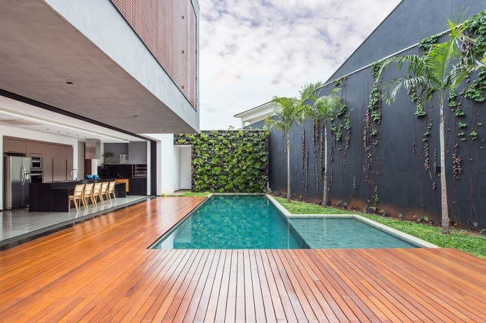 une piscine de luxe avec terrasse de bois, cuisine d'extérieur ouverte et un mur végétal extérieur