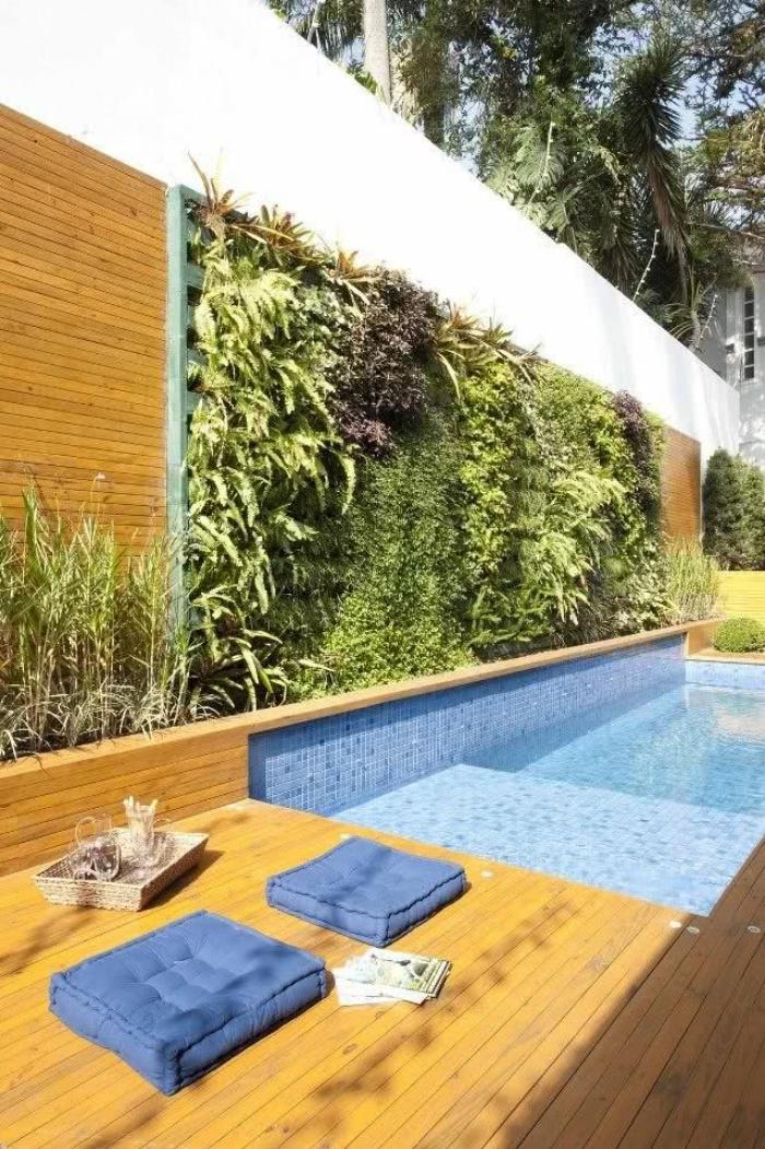 système de mur végétal d'extérieur aménagé tout au long de la piscine façon cloture vegetale qui créer un bel contraste avec la terrasse en bois et l'eau