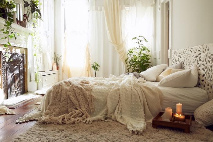 deco boheme chic dans une chambre blanche avec cheminée et grande fenêtre, déco de lit au sol avec têt ede lit blanche aux motifs mandala
