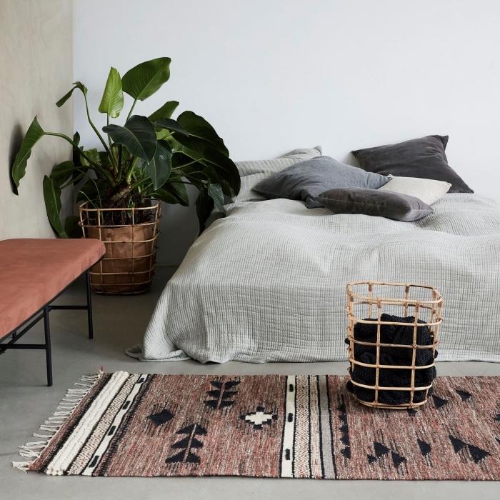 déco de pièce blanche avec pan de mur beige et plancher gris, modèle de tapis marron aux motifs géométriques blanc et noir avec franges