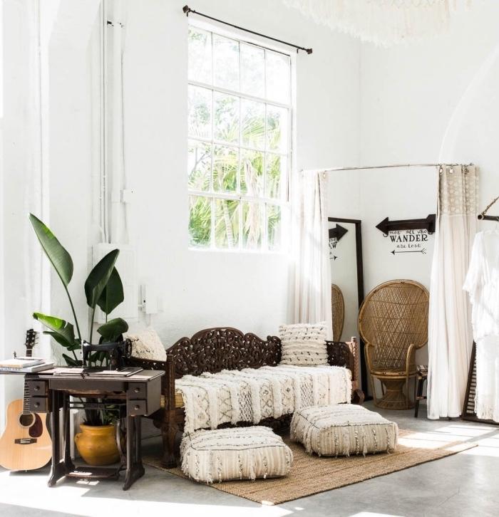 pièce de style bohème chic aux murs blancs et plancher design béton couvert de tapis beige et coussins bèrberes