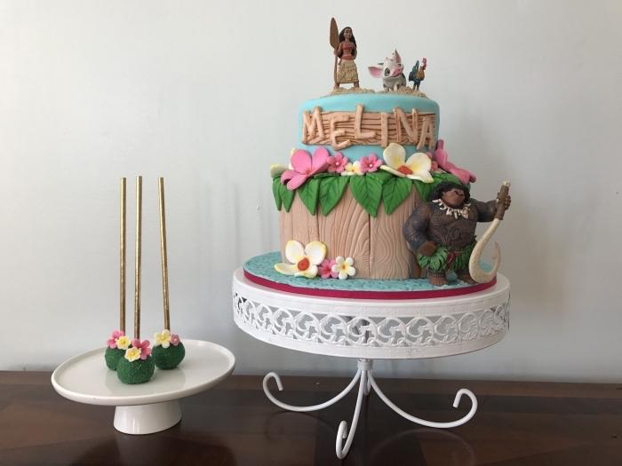 modèle de gateau anniversaire vaiana avec figurines des personnages Vaiana Maui Hei Hei et Pua, modelage art déco gâteau en pâte sucre