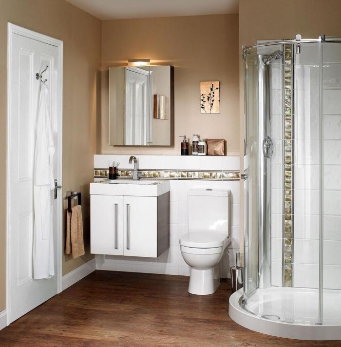 amenagement salle de bain petit espace aux murs beige avec plancher marron et équipement cuvette lavabo et cabine de douche en blanc