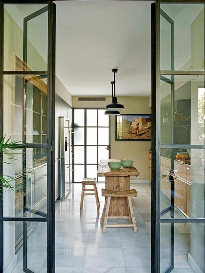 verrière porte coulissante, table en bois, lampes pendantes, tabourets en bois rustiques