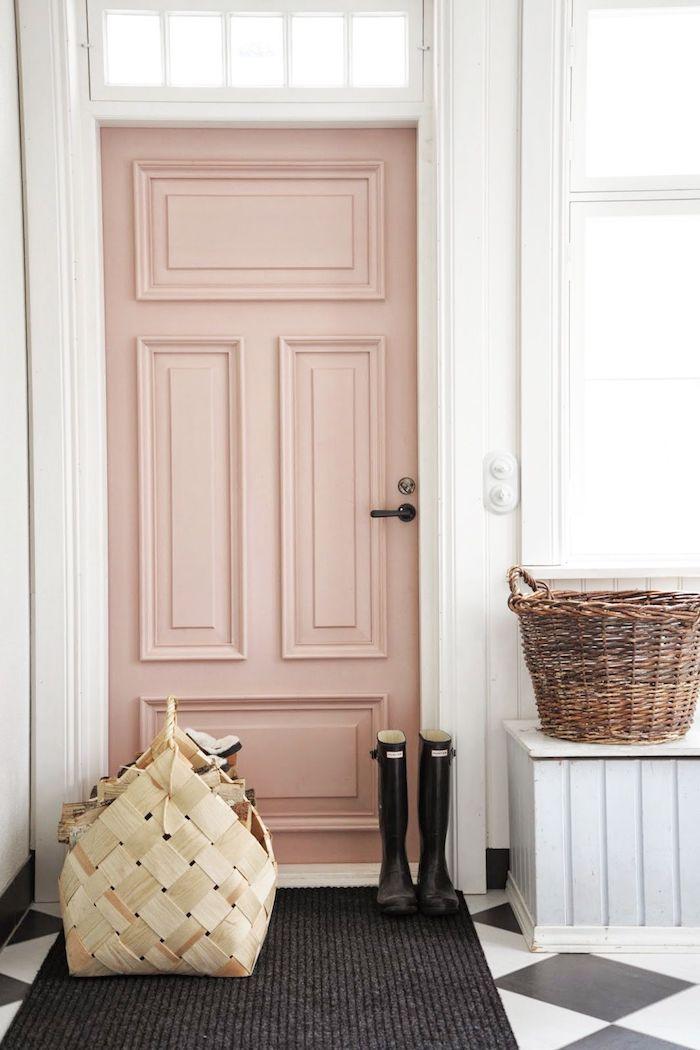 porte rose poudree, murs blancs, tapis noir, bottes en caoutchouc noir, deux grands paniers pour ranger ses affaires, carrelage en noir et blanc, motifs losanges