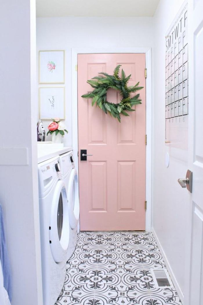 porte en couleur rose pale, rose poudree, espace avec machine a laver, carrelage aux motifs vintage en blanc et gris perle, porte blanche a l'autre bout de la pièce en longueur