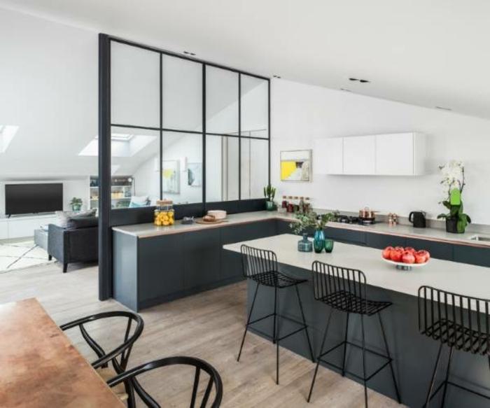 grande cuisine ouverte sur salon, grand ilot de cuisine, sol en bois, chaises de bar, cloison vitrée complète, murs peints blancs