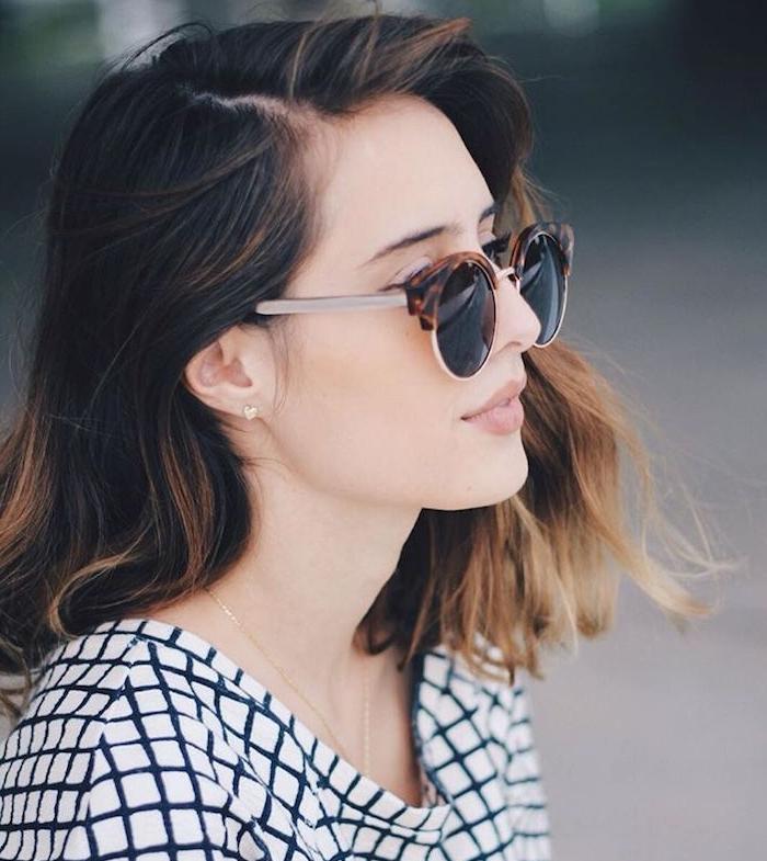 carré long flou avec des ondulations subtiles mal dessinées, lunettes de soleil monture originale, mèches miel dans cheveux chatain foncé