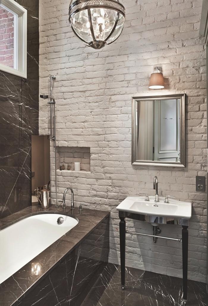 déco moderne salle de bain avec baignoire aux murs en briques blanches et carrelage noir avec baignoire et lavabo en blanc