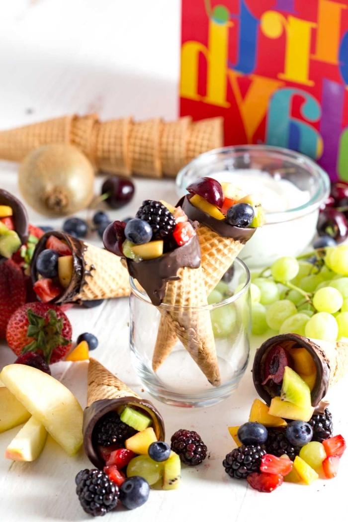 des cornets de glace chocolat et vanille remplis de salade de fruits frais, parfaits pour un brunch ou un buffet d'anniversaire