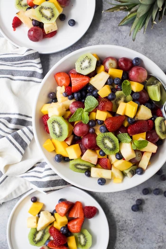 une salade été d'un mix de fruits pour les grandes chaleurs, parfumée à la menthe, salade composée originale de kiwi, fraises, ananas et mangue