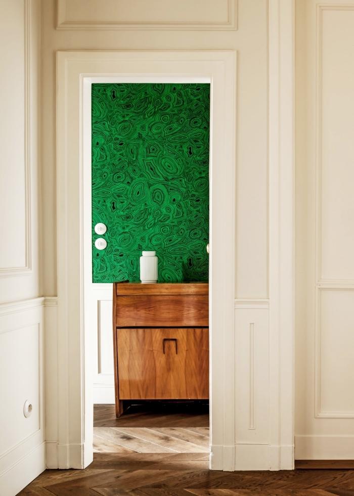 porte de chambre d'aspect vintage recouvert de papier peint vert malachite qui s'harmonise parfaitement avec le meuble en bois vintage et la boiserie blanche des murs