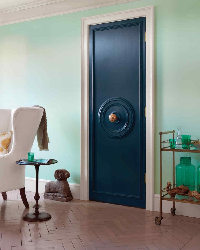 moulure porte en forme de rosace fixée au centre de la porte et peinte de la même couleur bleu nuit, agrémentée d'un joli bouton de tirage