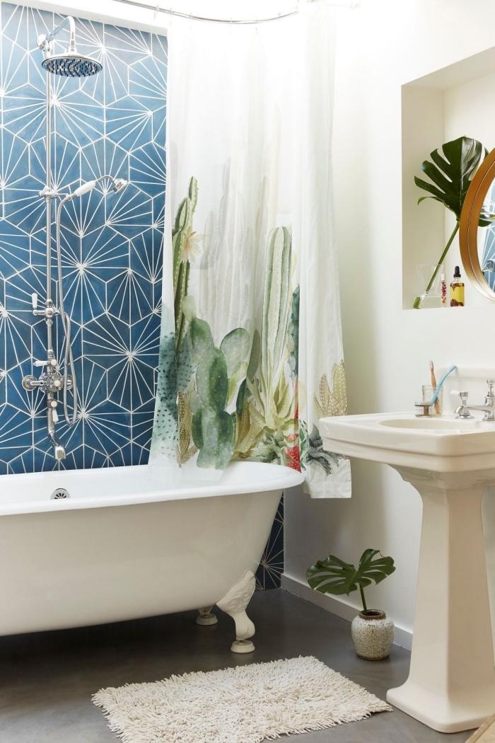 déco motifs tropicaux larges dans une petite salle de bain moderne aux murs blancs et sol imitation béton avec rideaux baignoire plantes