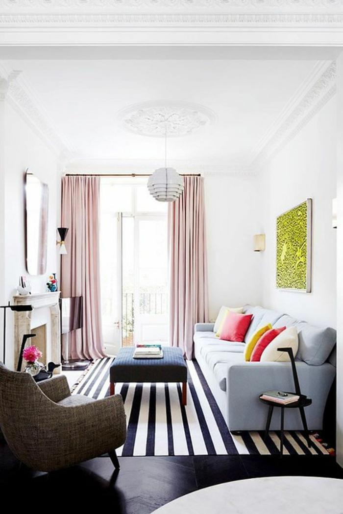tapis aux rayures verticales bleu marine et blanc,panneau décoratif au cadre blanc avec intérieur en vert réséda, canapé en gris clair, rideaux en couleur rose pale