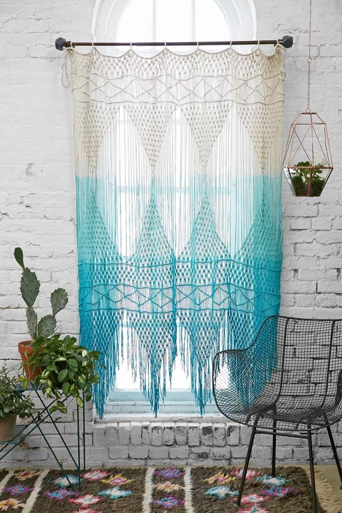 modèle de chambre boheme chic moderne aux murs en briques blanches avec rideaux fenêtre à design macramé ombré en bleu et blanc